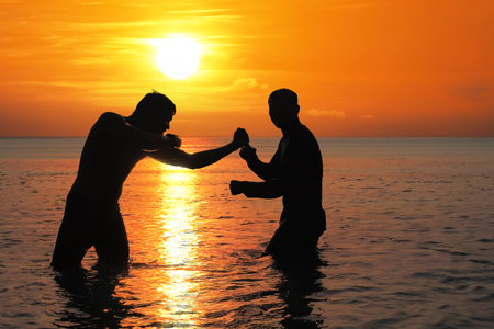 Asian man practicing Thai boxing on the sea beach at sunset.Thailand Stock fotó