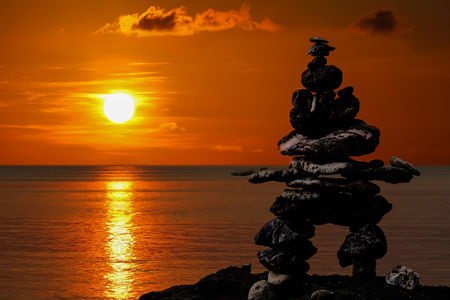 Stacked stones on the beach at sunset, red sky background. Фото со стока