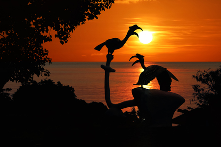 Silhouette of Birds Hornbill statue with trees and red sky sunset background.