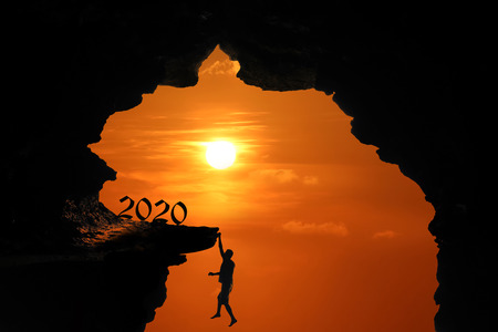 The Silhouette concept of new year 2020, Man jumping and climbing in the cave or high cliffs at a red sky sunset background.