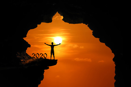 The Silhouette concept of new year 2020, Man standing and climbing in the cave or high cliffs at a red sky sunset background.