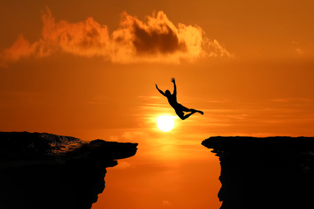 Silhouette of Men are jumped between high cliff at a red sky sunset background Фото со стока