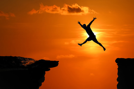 Silhouette of Men are jumped between high cliff at a red sky sunset background Stock fotó