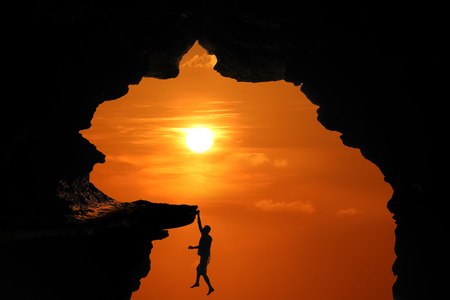 Silhouette of Man climbing in the cave or high cliffs at a red sky sunset background.