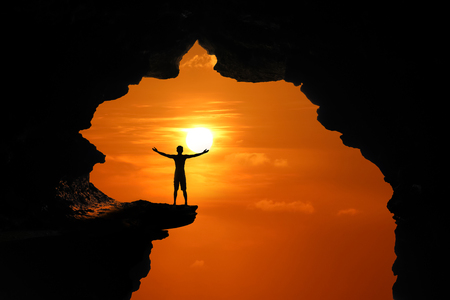 The man standing in a cave on a high cliff at red sky sunset background.