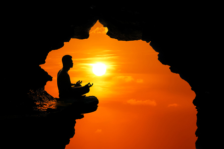 Man meditation and praying in the cave on the high cliff at sunset red sky background.