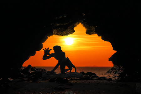 Caveman posture or action in the cave at red sky sunset background Stock Photo