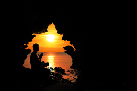 Man meditation and praying in the cave by the beach at sunset red sky background. Фото со стока
