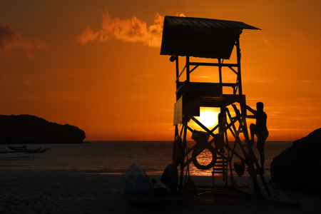 Lifeguard ready to take care of tourists on the beaches. Asian Lifeguard standing on the tower at sunrise in Thailand.