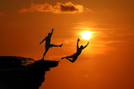 The concept of betrayal and the help of friends, Silhouette of Men are jumped between high cliff at a red sky sunset background Stock fotó