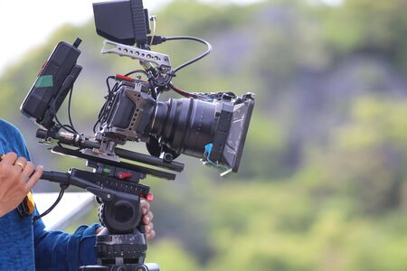 Videographer are shooting on the top of the mountain, Nature views background. Standard-Bild - 129552891