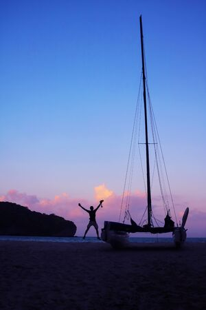 Men enjoying photography with camera near a sailboat on the beach in the evening after sunset.