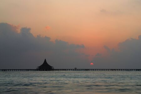 colour intensity: The sun rising over a Thai style hut in a Lagoon Stock Photo