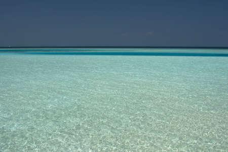 colour intensity: Beautiful shallow Maldivian Lagoon reflecting the mid-day sun. Stock Photo