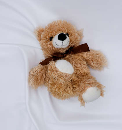 A light brown Teddy bear lies on a white knitted fabric