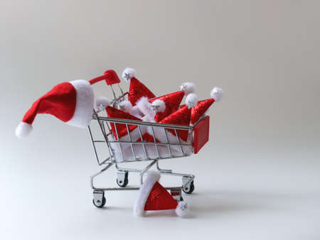 Lots of Santa hats in a stylized shopping basket. Preparing for the winter holidays. The concept of seasonal discounts and sales. Free space for copying