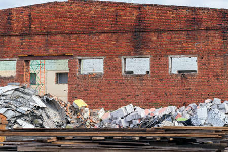 The ruined wall of an old red brick house with windows and no roof. In the foreground-a pile of construction debris. The concept of reconstruction of an outdated object for its use in new conditions