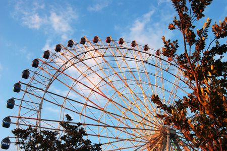 Large view of ferris wheel framed by trees right and bottom against blue cloudy sky Stock Photo - 3039505