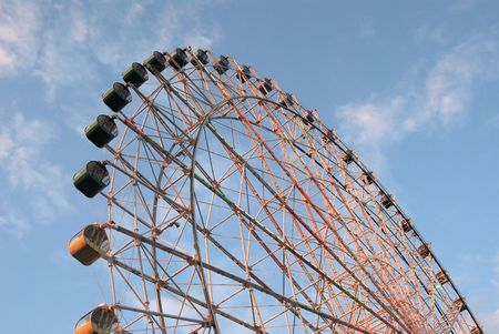 angled view: Tall angled view of ferris wheel against thin clouds