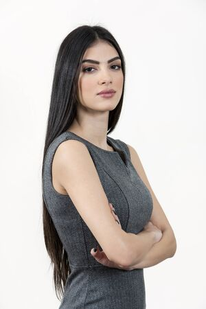 Young business woman standing with her arms crossed and looking at the camera. She has black long hair and wearing a grey dress. Stock Photo