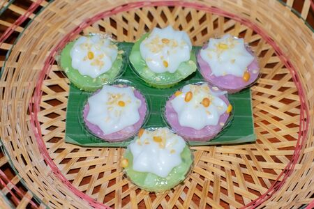 Thai Desserts(Ka-hnom Leum-Kleun) Mung Bean Flour in Jelly topping with coconut milk, soybean and sesame, colorful Thai desserts, Thailand traditional food.