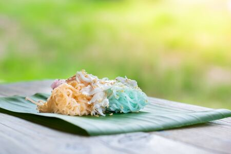 Thai Desserts (Ka-Nhom-Ray-Rai or Rang-rai ), Rice flour dumpling topped coconut milk and sugar mixed with sesame, colorful Thai desserts, Thailand traditional food. Stock Photo - 132667369