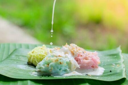Thai Desserts (Ka-Nhom-Ray-Rai or Rang-rai ), Rice flour dumpling topped coconut milk and sugar mixed with sesame, colorful Thai desserts, Thailand traditional food. Stock Photo