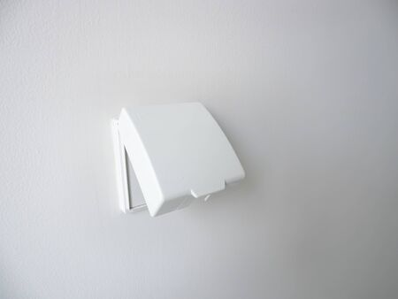 White external waterproof cover plug for use outdoor area on white wall background, double electrical plug socket, Electric safety concept.