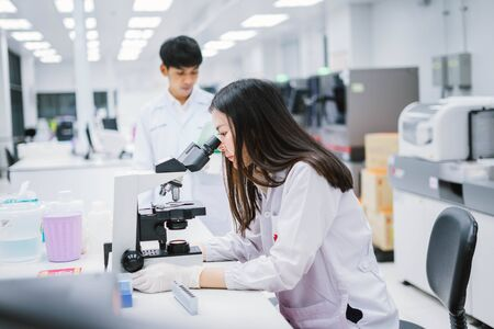 Two medical scientist working in Medical laboratory , young female scientist looking at microscope. select focus in young female scientist