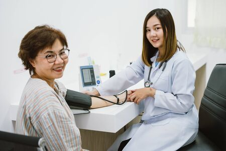 doctor checking senior patient blood pressure. Health care.