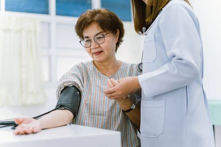 close up doctor checking senior patient blood pressure. Health care.
