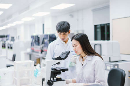 Two medical scientist working in Medical laboratory , young female scientist looking at microscope. select focus in young female scientist Zdjęcie Seryjne