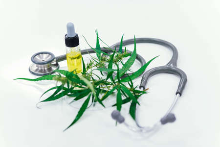 Marijuana plant and cannabis oil bottle on stethoscope