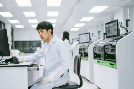 young male scientist looking results from automation blood analyzer report in computer and young female scientist working with automation blood analyzer at medical laboratory Standard-Bild