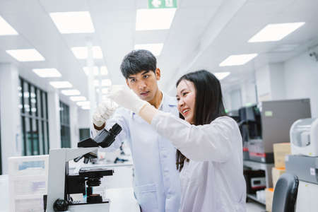 Two young medical scientist looking at test tube in medical laboratory , select focus on male scientist