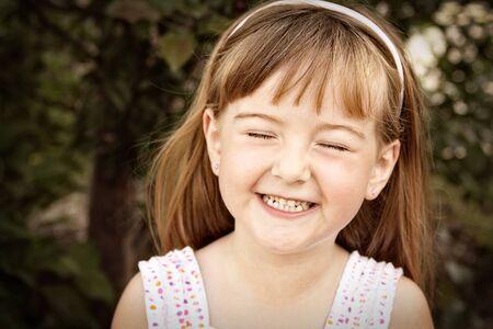 彼女は目を閉じて笑っている小さな女の子の肖像画