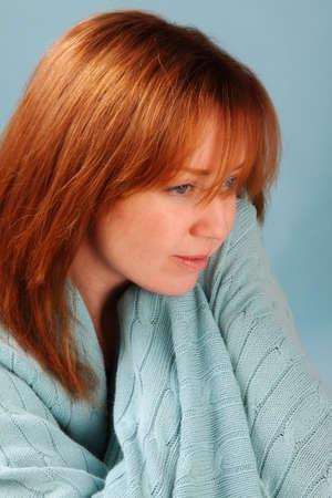 青い毛布を赤い頭の女性 写真素材