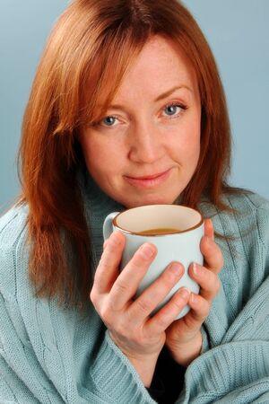 青色の背景とコーヒーを飲む女性