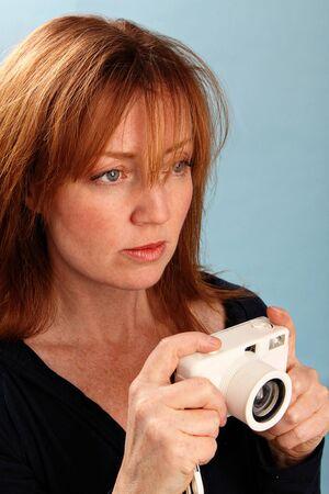 写真を撮るにカメラを持つ女性 写真素材
