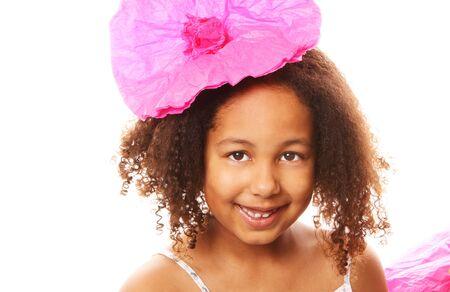 彼女の髪にピンクの紙で花を持つ少女