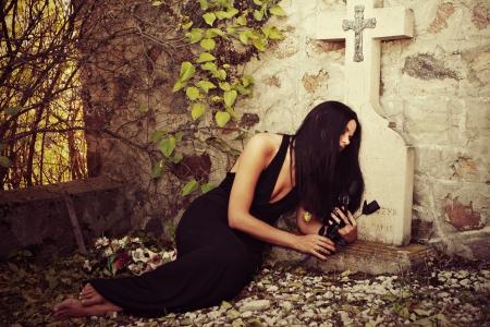 cementerios: una mujer que pone delante de la tumba de piedra