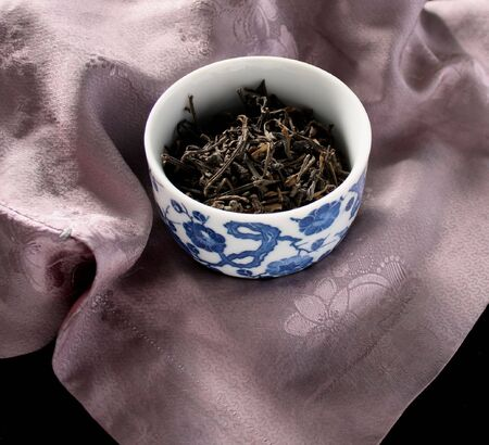 a blue and white teacup full of dried tea against a very old lavender-colored silk tunic