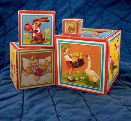 stackable: four very old childrens blocks with colorful illustrations of children and animals