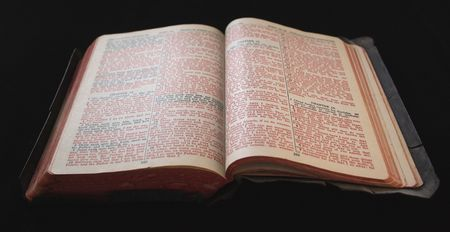 an old Bible with tattered edges and red and black text against a black background Stock Photo