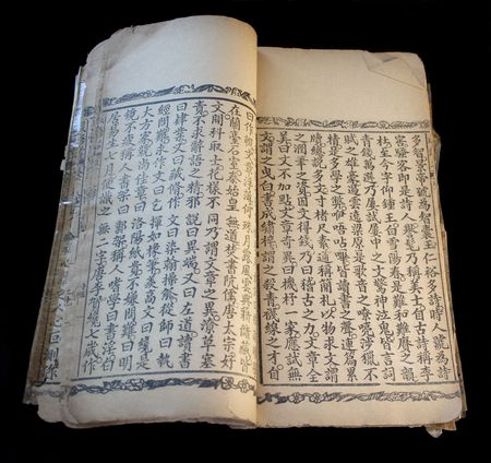 an old Chinese text with torn pages and decorative borders against a black background