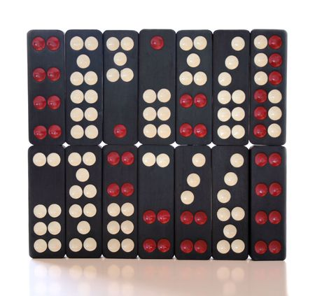 very old and well-used black red and white dominoes isolated against white