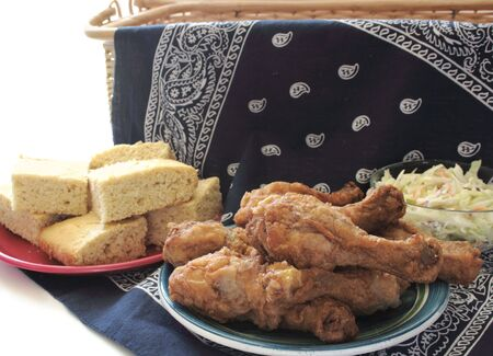 fried chicken legs, cornbread, and coleslaw on a dark blue bandana for a summertime picnic Banque d'images
