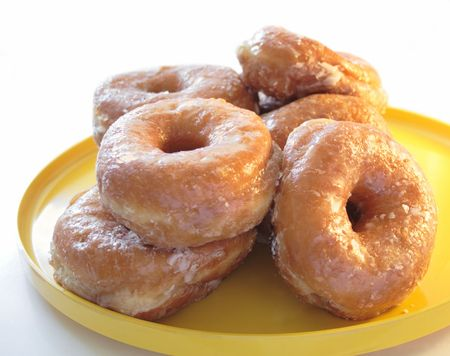 fresh glazed yeast doughnuts on a yellow plate
