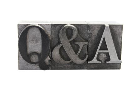 old, inkstained lead letterpress type forms the term 'Q&A' in all caps isolated on white