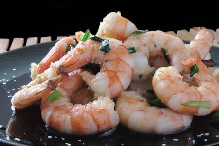 shrimp with scallions and kosher salt on a black plate on a wooden mat
